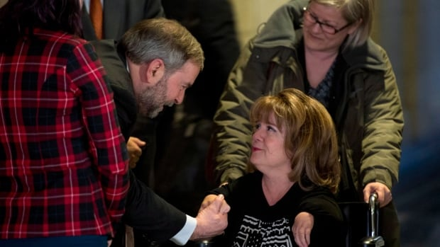 NDP Leader Tom Mulcair stops to speak with Mercedes Benegbi, who is a thalidomide survivor and executive director of the Thalidomide Victims Association of Canada, in the foyer of the House of Commons Monday. The federal government says it needs more time to determine how to help 95 surviving thalidomide victims.