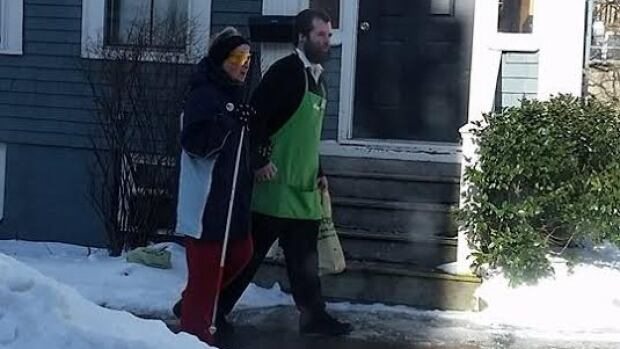 This photo of a Sobeys employee walking a 72-year-old customer home was posted to Facebook on Friday.
