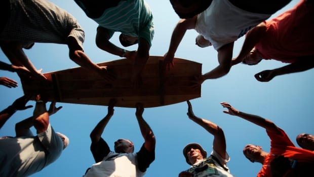Bosnian Muslims carry a coffin prepared for a mass burial near Srebrenica on the 2011 anniversary of a massacre during the Balkan wars that saw 8,000 Muslim men and boys slaughtered and buried in mass graves in 1995. The UN ruled neither Serbians nor Croatians committed genocide during the 1990s conflict.
