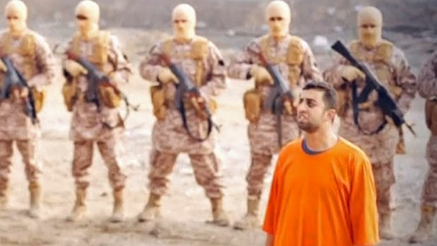 Jordanian pilot Muath al-Kasaesbeh stands in front of armed men in this still image from an undated video released by Islamic State militants on Tuesday. The video purports to show Kasaesbeh being burnt alive, and Jordanian state television said he was murdered a month ago.