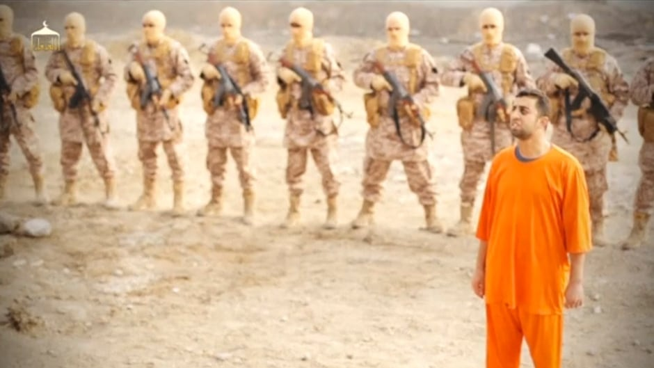 "A man purported to be Islamic State captive Jordanian pilot Muath al-Kasaesbeh stands in front of armed men in this still image from an undated video filmed from an undisclosed location made available on social media on February 3, 2015. According to Aymenn Jawad Al-Tamimi, the soundtrack to this video is a jihadi nasheed, or song, called ""Soon, Soon""."