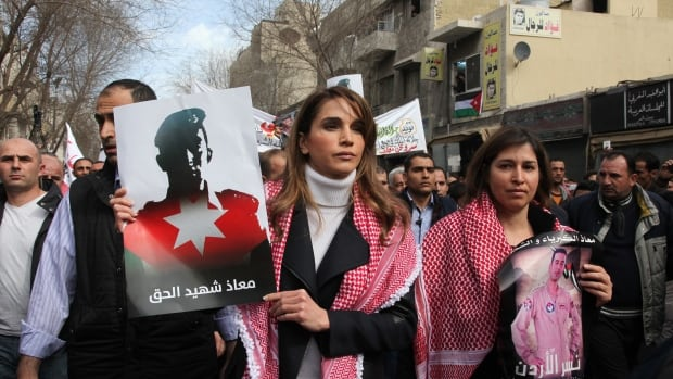 Jordan's Queen Rania  holds a picture of recently executed Jordanian pilot Muath al-Kasasbeh, with the words in Arabic reading 'Muath is a martyr of right.' Jordan has stepped up its fight against ISIS in Syria in light of the pilot's death.