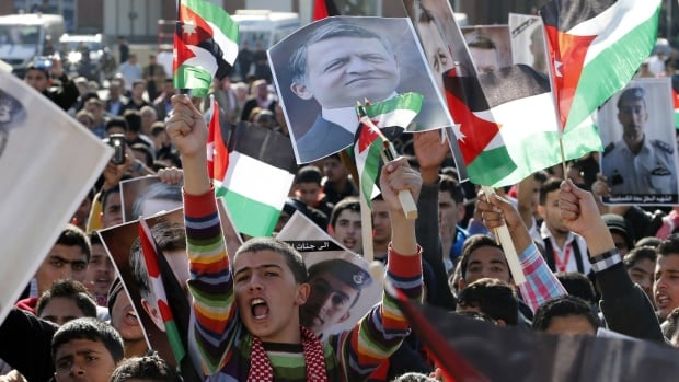 Protesters hold up pictures of Jordan's King Abdullah and pilot Muath al-Kasaesbeh, who was killed by ISIS militants.  Jordan's air force has vowed to wipe out the militants.