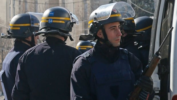 French riot police officers secure the access to the Castellane housing area in Marseille on Monday after hooded gunmen armed with Kalashnikov rifles fired on police.