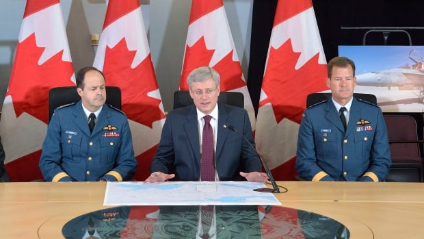 Chief of the Defence Staff Tom Lawson (left) has appointed a new commander for the Royal Canadian Air Force: Major-General Michael Hood (right), seen here announcing the military's deployment to Central and Eastern Europe in April, 2014.