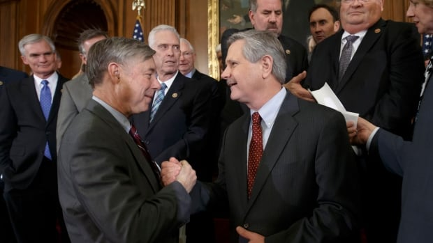 House Energy and Commerce Committee Chairman Fred Upton, R-Mich., left, clasps hands with Sen. John Hoeven, R-N.D., sponsor of the Senate's Keystone XL pipeline bill version, as lawmakers gather to urge President Barack Obama to sign the legislation passed in the House and Senate approving expansion of the Keystone XL pipeline, at the Capitol in Washington.