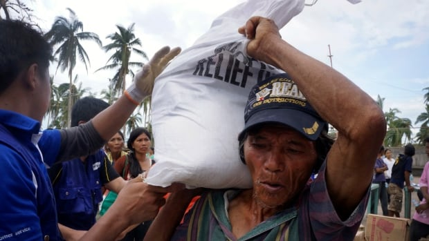 Workers from the charity World Vision distribute aid in northern Cebu, Philippines. If you want to claim a tax credit for your donations to charities, check CRA's websites to ensure they are registered with the tax agency.