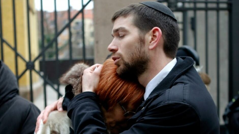 Denmark's chief rabbi, Jair Melchior, comforts a woman at a memorial site in Copenhagen.
