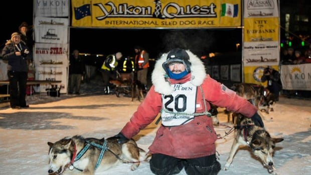 Ed Hopkins poses while two of his dog team chow down on some well-earned treats after finishing third in this year's Yukon Quest.