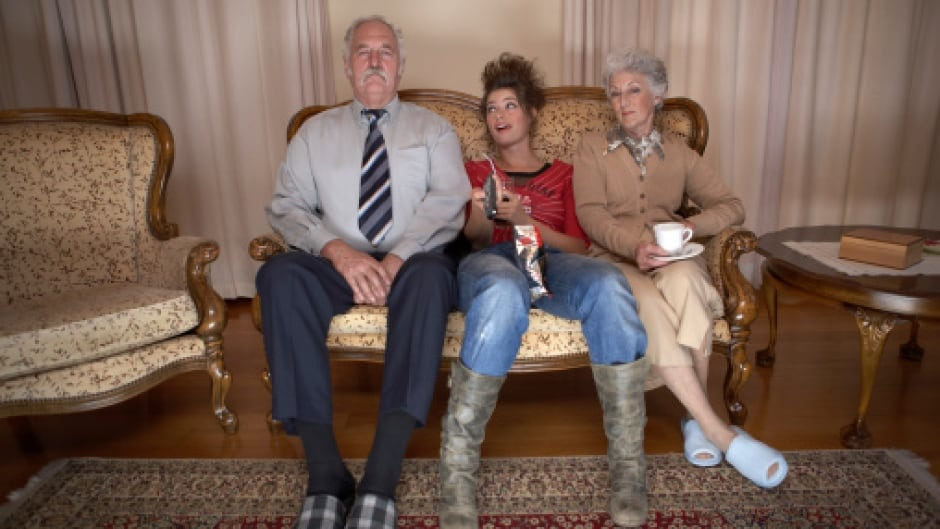 Adult daughter sitting between senior couple on settee