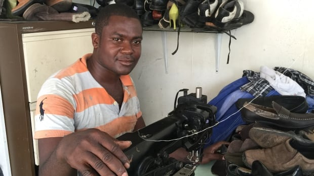 Cobbler Charles Oduro sews a pair of leather shoes in Kokomele neighbourhood in Accra, Ghana. His business is often idle for one to three days due to power outages.