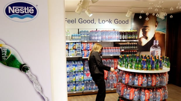A Nestlé employee takes bottles of water from the firm's supermarket for staff at its headquarters in Vevey, Switzerland. Starting in 2016, Nestlé Waters Canada will be charged $2.25 for every one million litres of groundwater it draws for its bottling plant in Hope, B.C.
