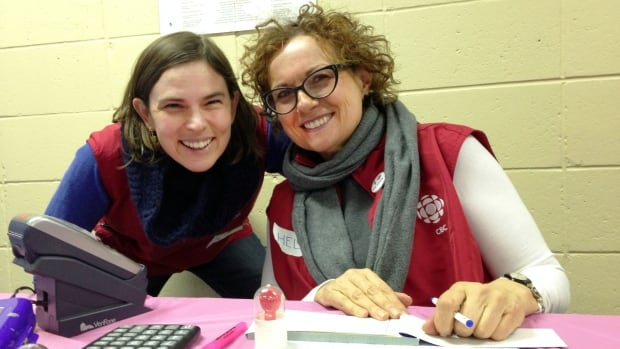 Monique and Do Crew volunteer Helen Becher man the silent auction table at Saturday night's CWHL fundraising game.