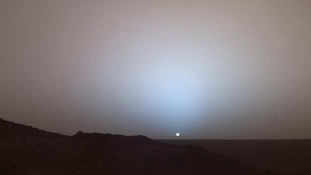 Dust in Mars's atmosphere scatters blue light in the forward direction, creating a bluish sky glow near the setting sun, as in this photo taken the Spirit rover in 2005.