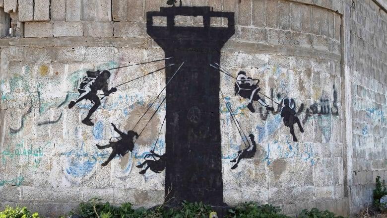 https://i.cbc.ca/1.2976424.1425071027!/fileImage/httpImage/image.jpg_gen/derivatives/16x9_780/banksy-gaza.jpg
