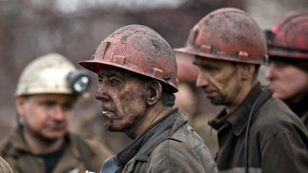 Ukrainian coal miners wait for a bus after returning to the surface of the Zasyadko mine in Donetsk, Ukraine. An explosion ripped through a coal mine before dawn Wednesday, killing at least 24 people.
