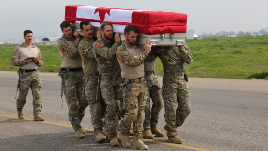 Pallbearers from the Canadian Special Operations Regiment (CSOR) carry the casket of their fallen comrade, Sgt. Andrew Joseph Doiron, during the ramp ceremony at the Erbil International Airport in Iraq on Sunday.