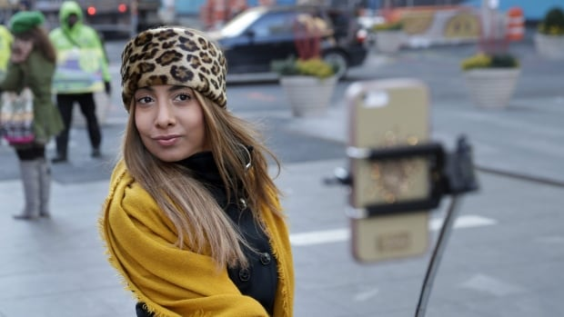 Sandy Johal uses a selfie stick to take a picture of herself in Times Square in New York, Thursday, Jan. 8, 2015. Several Montreal museums are banning selfie sticks in order to protect their art and artifacts.