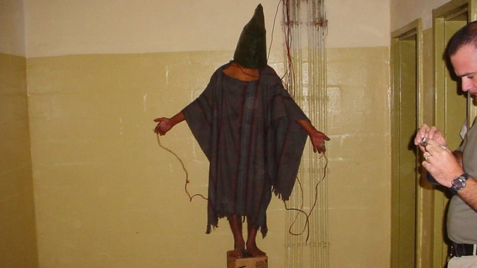 This image shows an unidentified detainee at the Abu Ghraib prison in Baghdad, Iraq, standing on a box with a bag on his head and wires attached to him.  (2003)