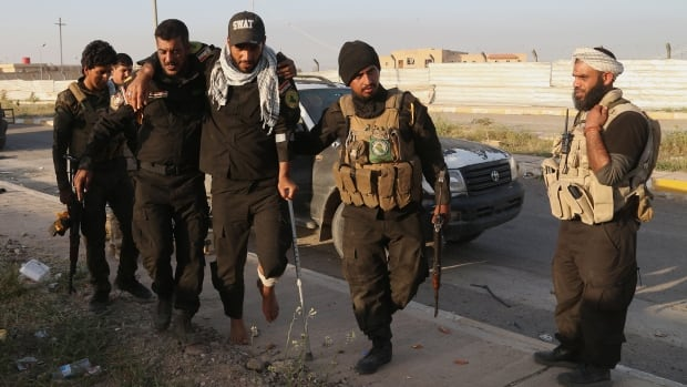 Members of an Iraqi Shia militia help a wounded colleague outside the Qadisiyya neighbourhood of Tikrit, 130 kilometres north of Baghdad. Iraqi military officials say the former home of Saddam Hussein will be retaken from ISIS in the next two or three days.