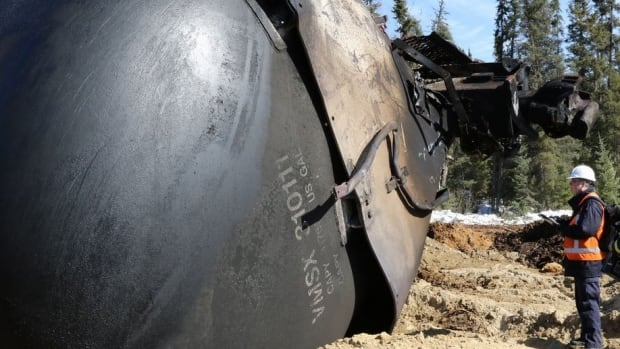 A Transportation Safety Board investigator stands beside a damaged tank car, near Gogama, in northern Ontario.