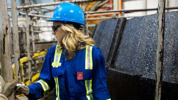 A tour guide walks around oil tanks during a tour at the Suncor tar sands operations near Fort McMurray, Alberta. A TD report says Alberta's financial problems extend far beyond the temporary plunge in crude prices.