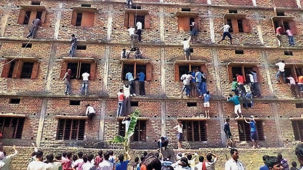 In this Wednesday, March 18, 2015 file photo, Indians climb the wall of a building to help students appearing in an examination in Hajipur, in the eastern Indian state of Bihar. Education authorities in eastern India say 600 high school students have been expelled after they were found to have cheated on pressure-packed 10th grade examinations. (AP Photo/Press Trust of India, File)