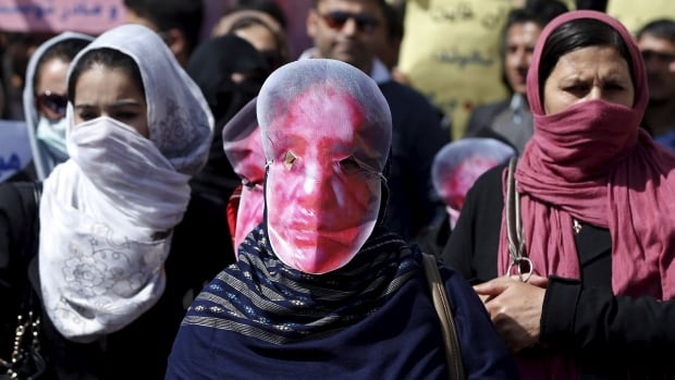 Afghans from the Hmbastagi party (Solidarity Party of Afghanistan) wear masks during a Monday protest to condemn the killing of 27-year-old woman, Farkhunda, who was beaten with sticks and set on fire by a crowd of men in central Kabul in broad daylight on Thursday.