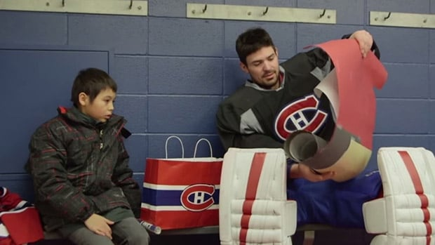 Canadiens star goalie Carey Price, right, and Trent Leon, both from Anahim Lake, B.C., exchange gifts at Montreal's training centre.