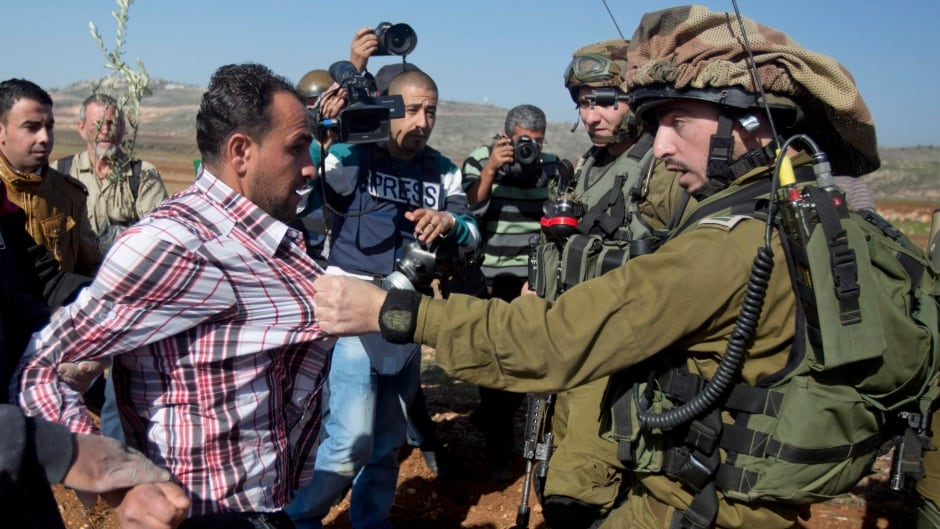 A confrontation between an Israeli soldier and a Palestinian during a demonstration against Israeli settlements in the village of Turmus Aya near the West Bank city of Ramallah, Wednesday, Dec. 10, 2014.