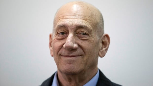 Former Israeli Prime Minister Ehud Olmert smiles as he waits in a court room in Jerusalem's District Court on Monday. The court later found Olmert guilty of accepting bribes in a retrial of corruption charges.