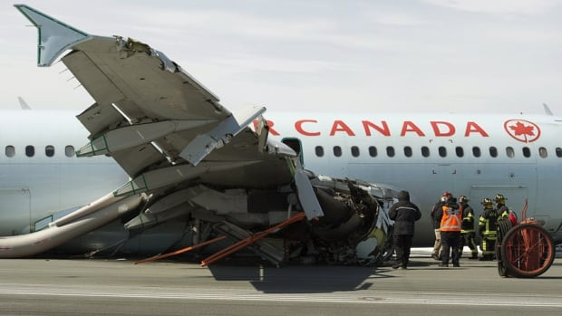 Transportation Safety Board investigators and airport firefighters work at the crash site of Flight AC624 at Stanfield International Airport in Halifax.