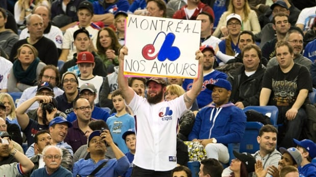 Fans wear Expos uniforms as they watch the Toronto Blue Jays in a pre-season game against the New York Mets last year in Montreal.