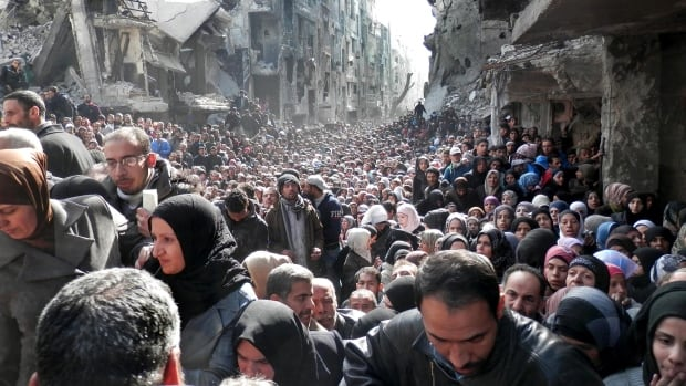 Residents of the besieged Palestinian camp of Yarmouk line up for supplies in 2014. Most of the camp has been seized by ISIS, who are fighting a Palestinian group inside the camp.