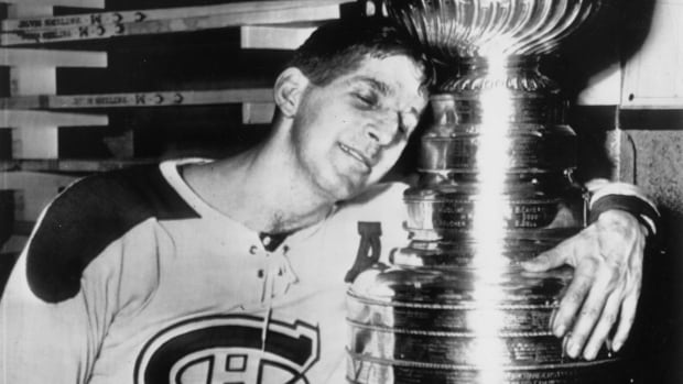 Veteran Canadiens centre Elmer Lach hugs the Stanley Cup in the dressing room of the Montreal Forum in Montreal, Que., on April 16, 1953, after scoring the only goal in the fifth game of the Stanley Cup playoffs with the Boston Bruins. Lach scored the goal at 1:22 of a sudden death overtime period to give his team a 1-0 triumph.