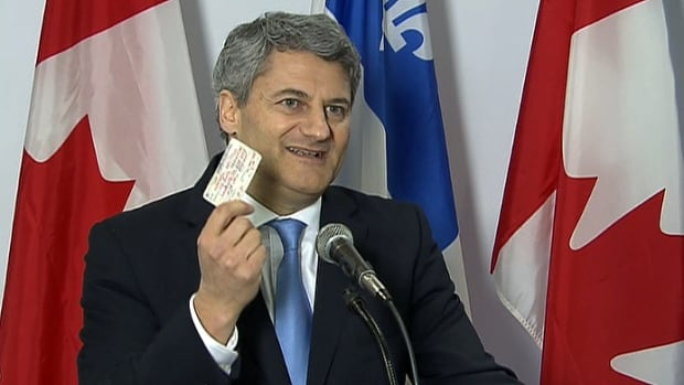 Gérard Deltell holds up his Conservative party membership card that he signed in 1981.