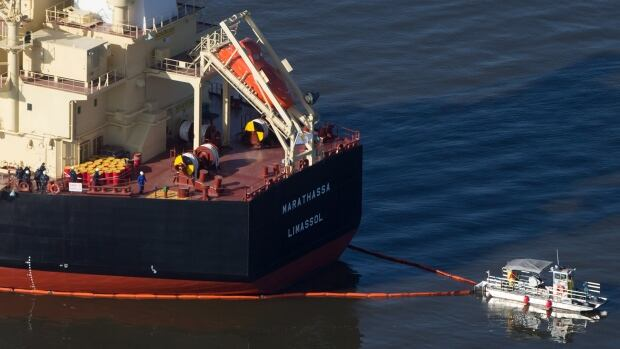 A spill response boat secures a boom around the bulk carrier cargo ship Marathassa after a bunker fuel spill on Burrard Inlet in Vancouver, B.C., on Thursday April 9, 2015.