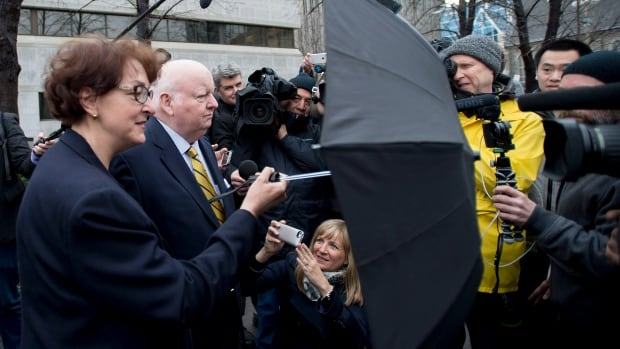 Heather Duffy, wife of suspended Senator Mike Duffy, uses an umbrella to block members of the media as she waits with her husband after leaving the courthouse in Ottawa on Friday.