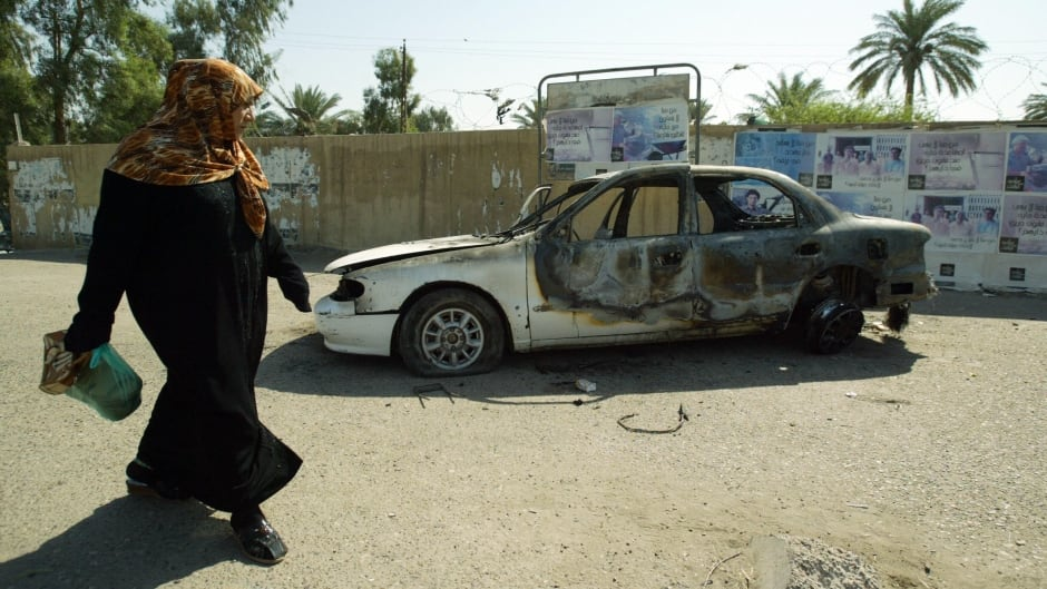 An Iraqi woman walks past a burnt car at the site where Blackwater guards who were escorting US embassy officials opened fire in the western Baghdad neighbourhood of Yarmuk.