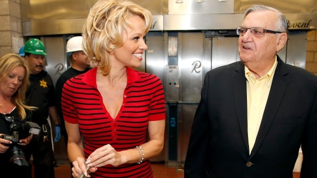 Actress Pamela Anderson, left, joins Maricopa County Sheriff Joe Arpaio as they serve an all-vegetarian meal to inmates at the Maricopa County Jail on Wednesday in Phoenix.
