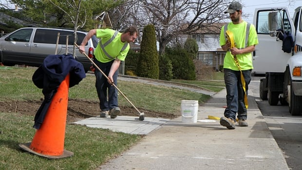 Workers from DICAM Landscaping of Binbrook lay a concrete pad for a future Canada Post super mailbox last week. The city is applying to Ontario court to restrain Canada Post from installing more mailboxes.