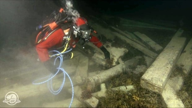 A diver with Parks Canada's underwater archaeology service inspects the remains of HMS Erebus underneath the Arctic sea ice in 2015.