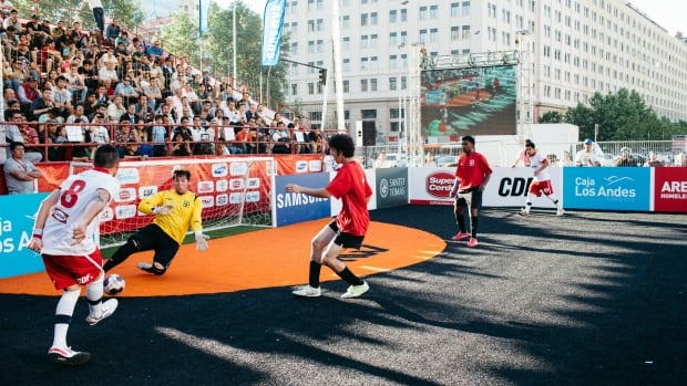 The 2014 Homeless World Cup, seen here was played in Chile. Canada is defending in this photo, dressed in the red jerseys.