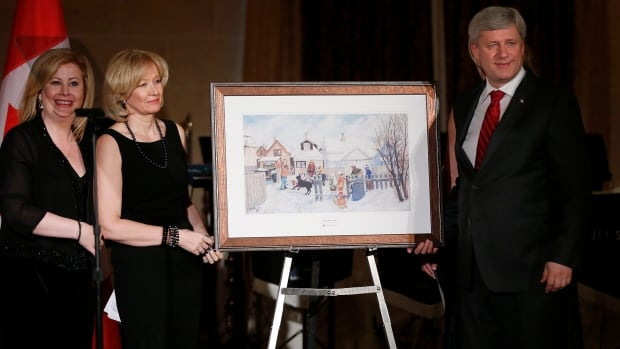 Prime Minister Stephen Harper, right, with his wife Laureen are presented with a painting from Lianna McDonald, executive director of Canadian Centre for Child Protection, at an event in Winnipeg to mark the centre's 30th anniversary on Friday evening.