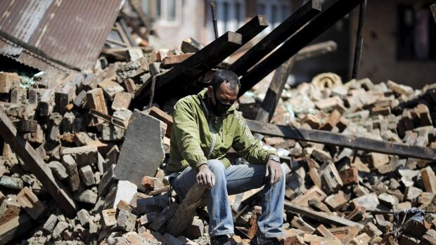 A man sits amid the rubble of his damaged house following Saturday's earthquake in Bhaktapur, Nepal. Relief pledges are pouring in, but getting workers and supplies into the country is proving to be a challenge.