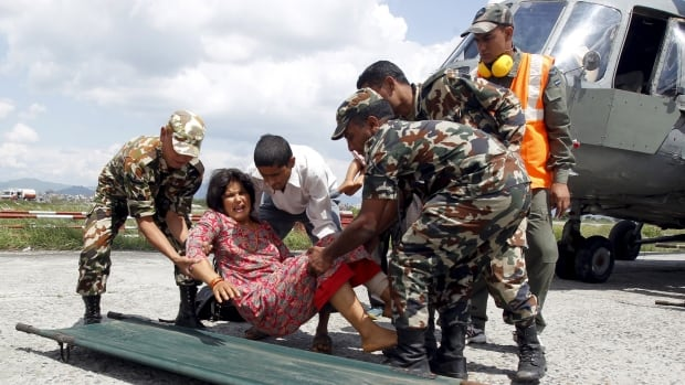 Indian Army soldiers place an injured woman, who was wounded in Saturday's earthquake, on a stretcher after she was evacuated from Trishuli Bazar to the airport in Kathmandu.
