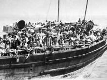 A group of refugees (162 persons) arrive on a small boat which sank a few meters from the shore in Malaysia. The flight of Vietnamese refugees began after the fall of Saigon in 1975.