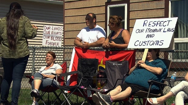 People in Kahnawake, Que., protested in front of the home where a Mohawk man and his non-native wife live. Mixed couples are prohibited by the territory's law from living on Mohawk land.