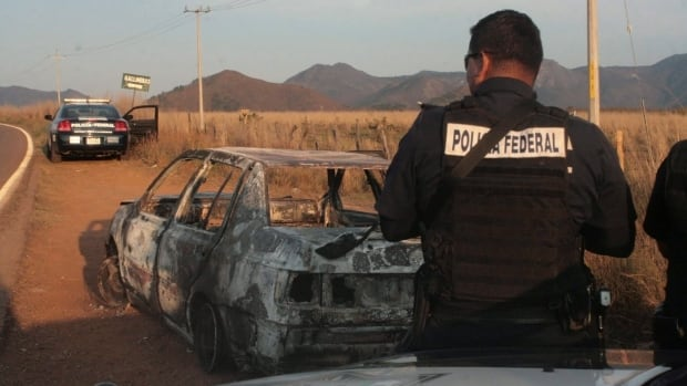 Mexican federal police stand next to a bullet riddled and burned car after a criminal gang ambushed a police convoy near the town of Soyatlan, near Puerto Vallarta, Mexico, April 6, 2015.