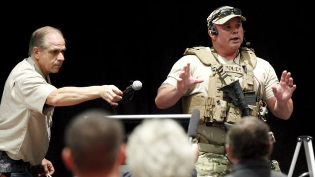 A police officer briefs the crowd of the Muhammad Art Exhibit and Contest in Garland, Texas, after it was reported that shots were fired outside the venue and a man is down.